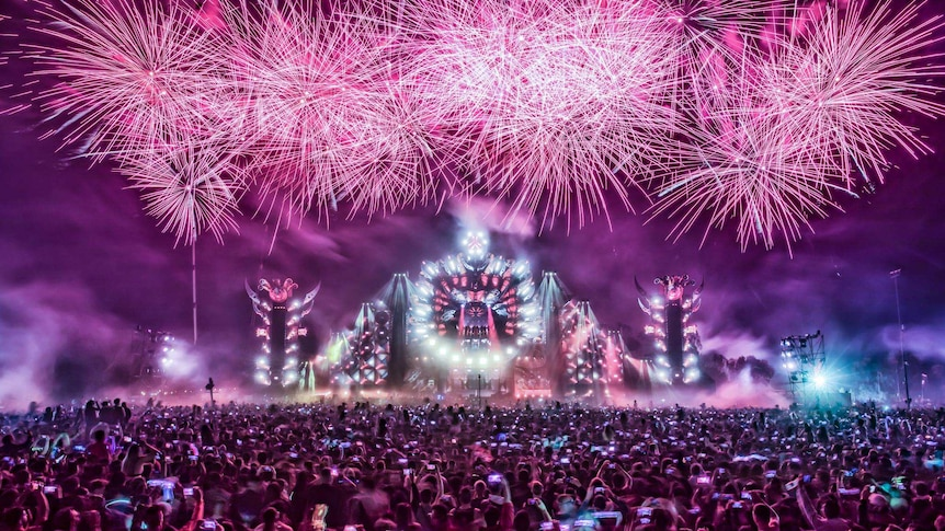 Fireworks over a stage in front of a crowd.