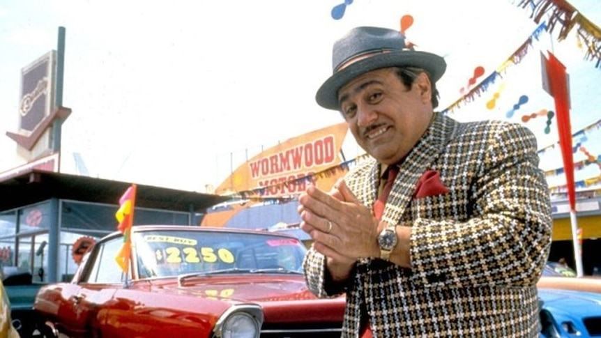 Actor Danny DeVito looks mischievous while standing in front of a used car yard in the film Matilda.