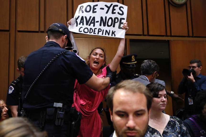 A protester holding a sign is escorted out of Brett Kavanaugh's Senate confirmation hearing.