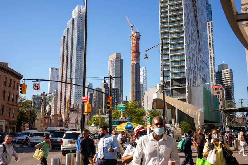 People walk in a street as a skyscraper is under construction in the background.