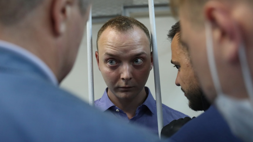 A closeup photo of a man's face between two bars speaking to several other man.