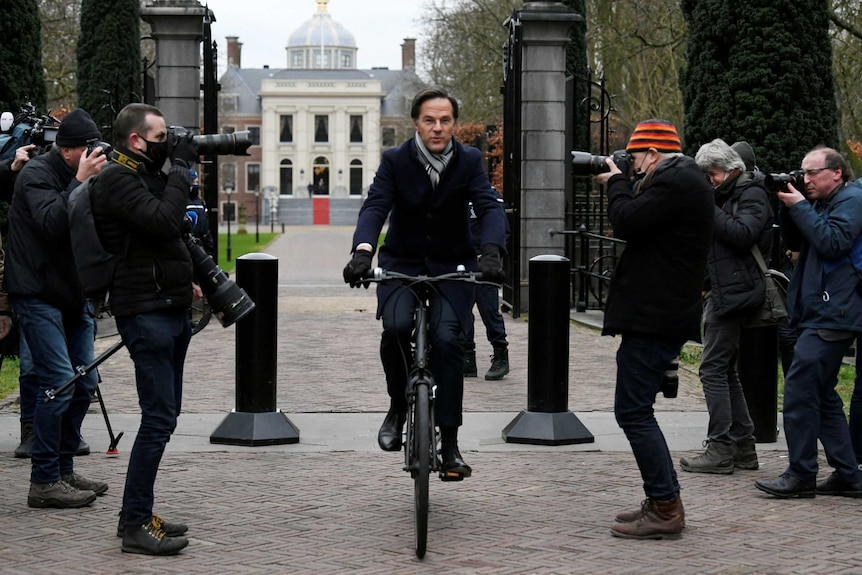 A man wearing a scarf and gloves cycles through gates.