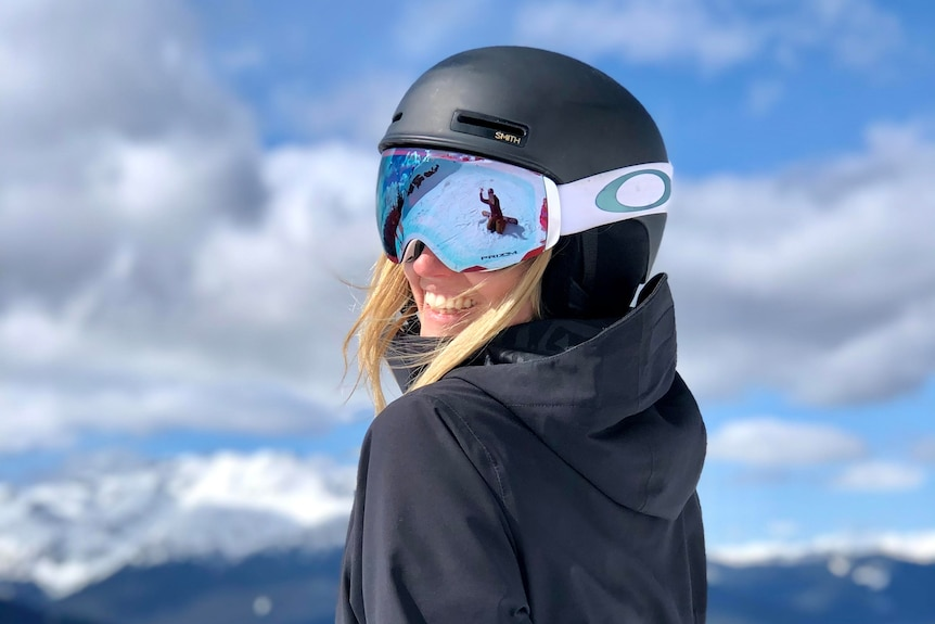 A woman in a ski helmet and goggles poses for a photo