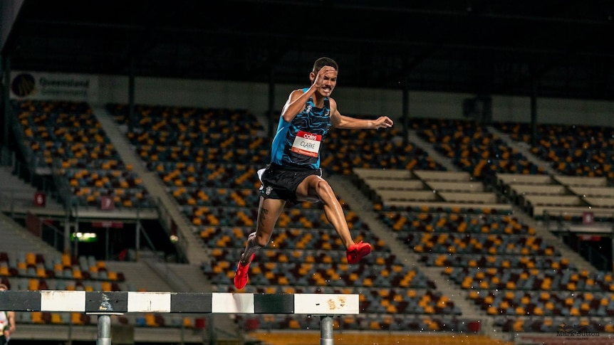 Matthew Clarke jumps over a steeple in a race with an empty stand in the background.