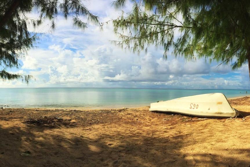 Enewetak lagoon on the Marshall Islands with upturned small boat on beach.