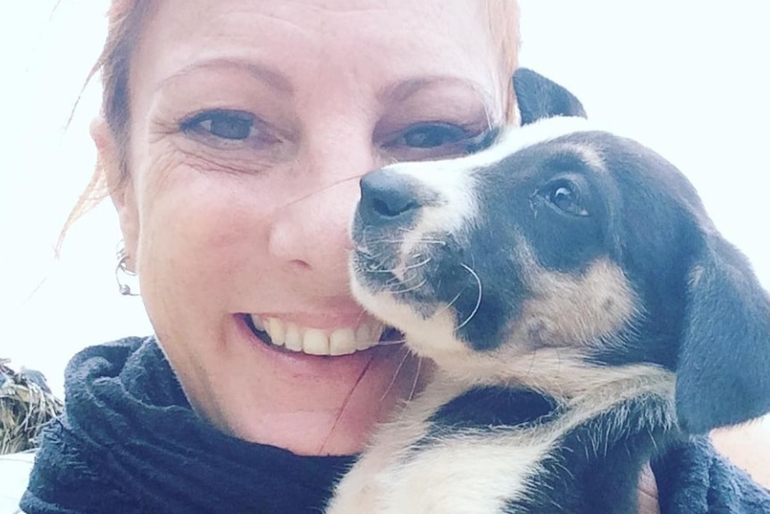 Angela Glover holds a small puppy near her face and smiles.