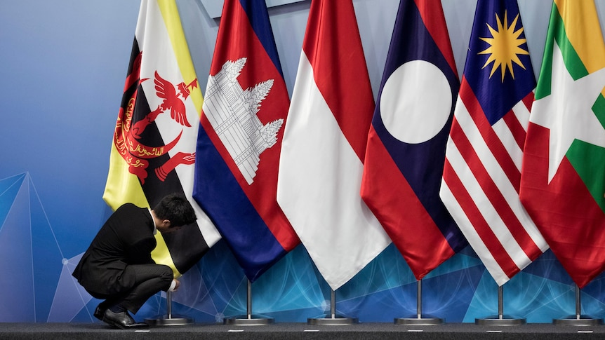 A worker adjusts Brunei's flag alongside Cambodian, Indonesian, Lao, Malaysian and Myanmar flags
