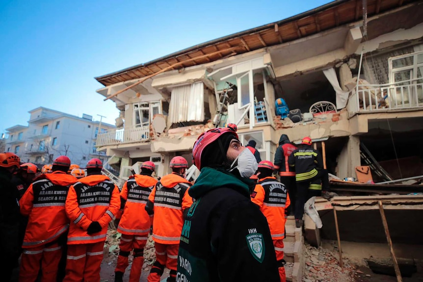 Rescuers search for people buried under the rubble on a collapsed building.