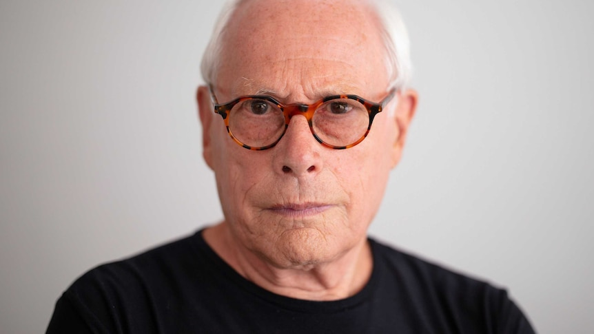 A man with white hair and glasses looks at the camera.