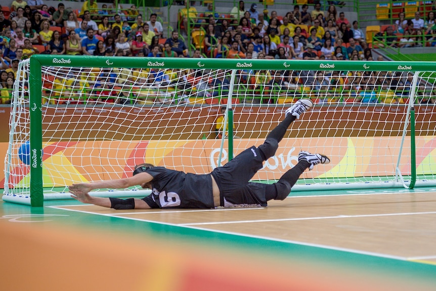 The ball goes into the net as a defender in goalball dives full length in a vain attempt to stop a goal.