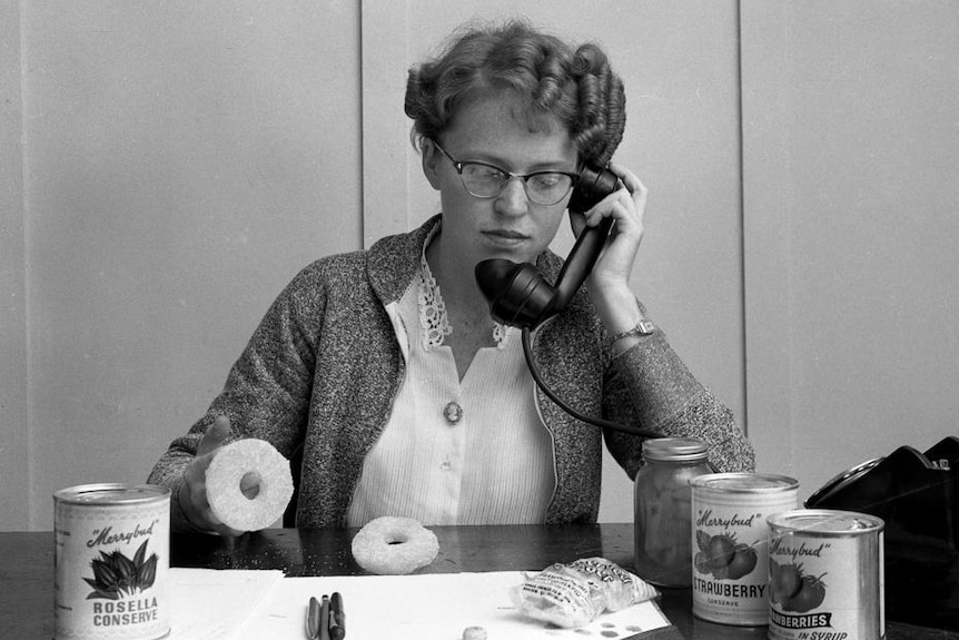Black and white photo of a woman on the phone at her desk.