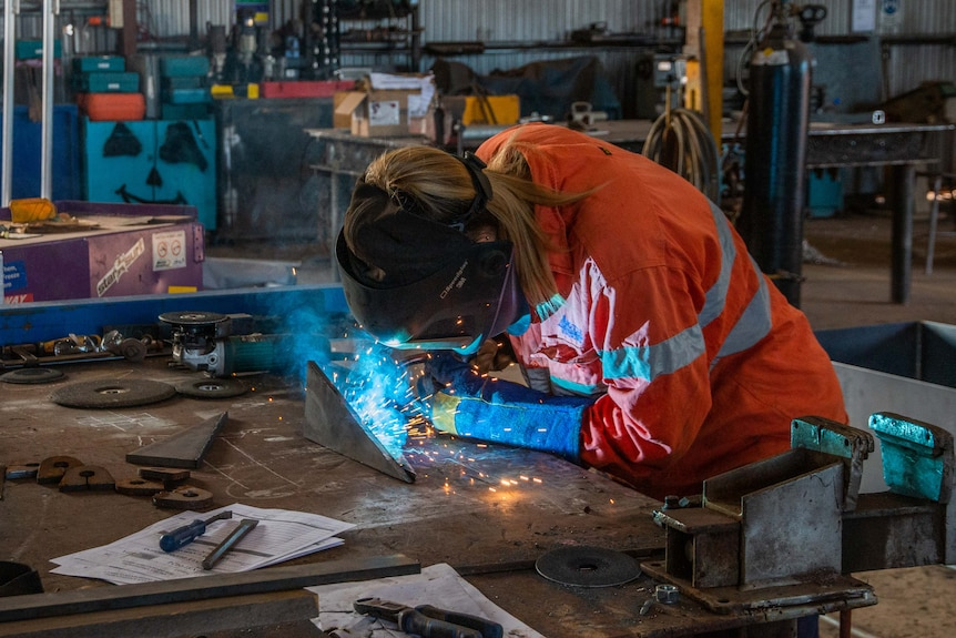 Woman with welding helmet on and fusing two pieces of metal together.