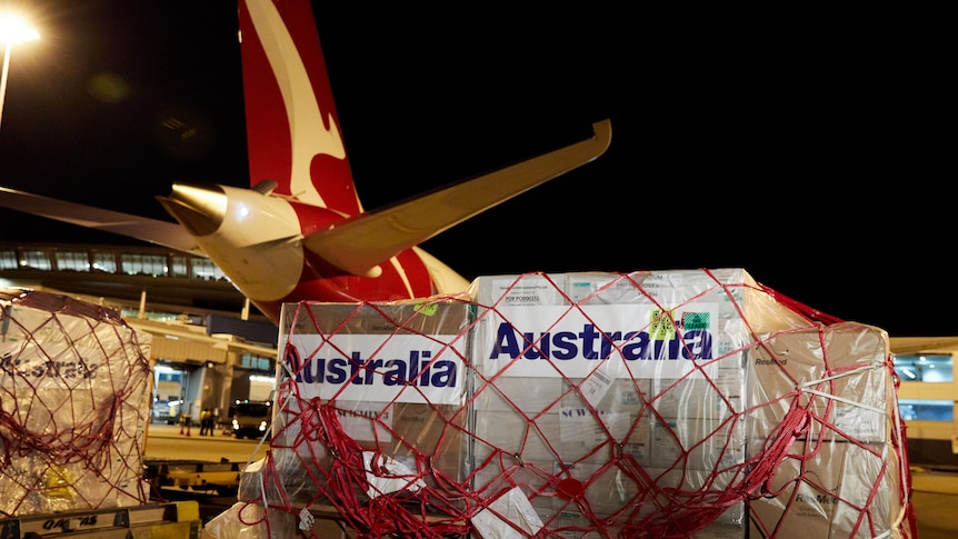 A Qantas plane sits on a tarmac, being loaded with wrapped containers of COVID-19 supplies