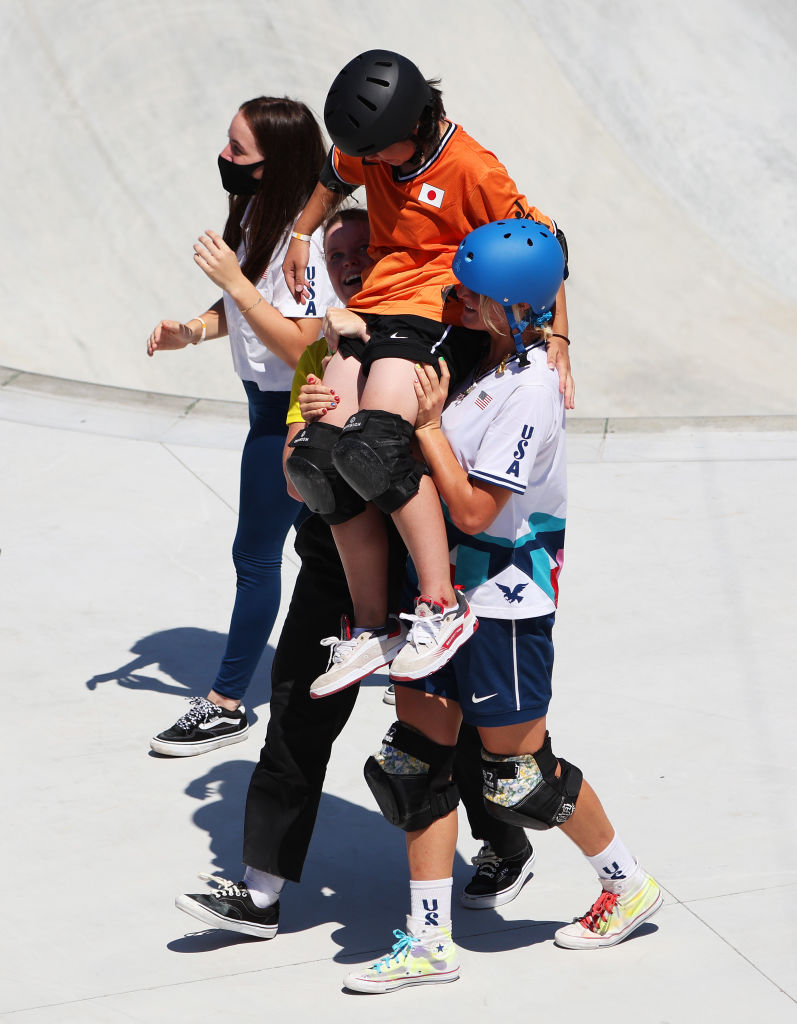 Two girls carry a third girl on their shoulders around a skate bowl, they are all wearing helmets and knee pads and are smiling