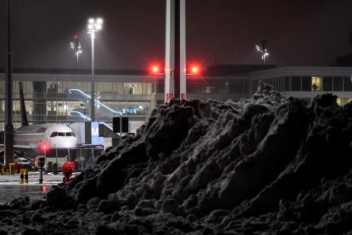 A mound of snow stands in the foreground with a plane in the background and airport behind it in the dark.