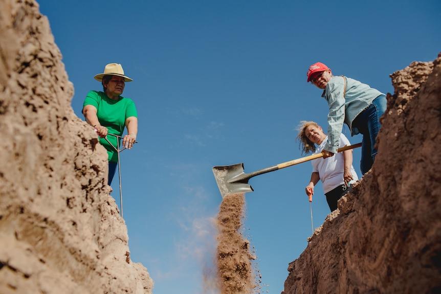 Three women shovel dirt.