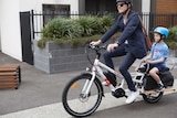 A commuter and child ride an electric cycle