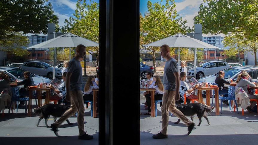 A man walks past cafes and restaurants on a street in Canberra.