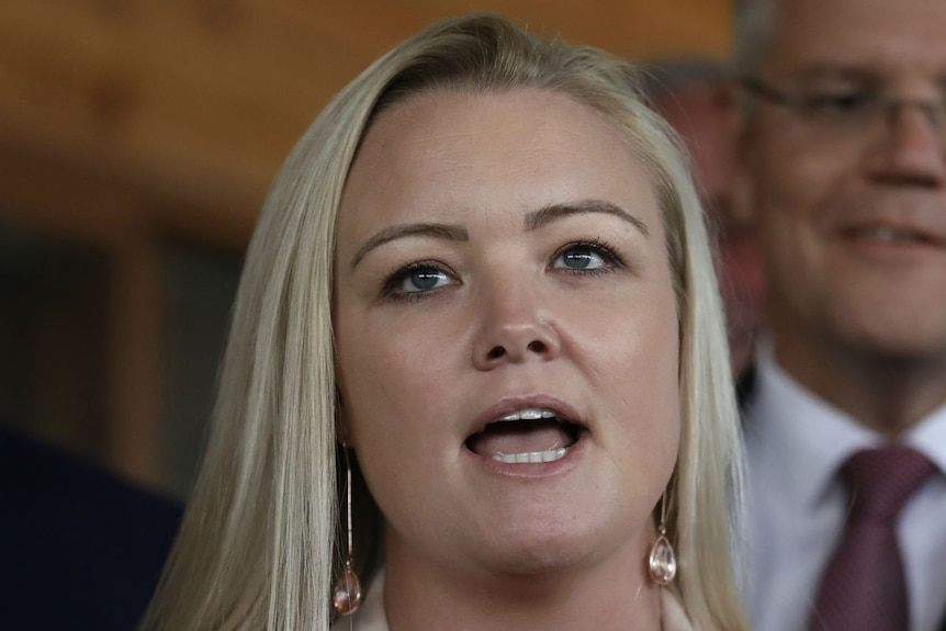 A woman with blonde hair, wearing a beige blazer, speaks to reporters. Scott Morrison stands behind her