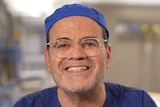 Daniel Lanzer, wearing a surgeon's scrubs, smiles, looking at the camera. He appears to be sitting in a surgery.