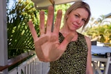 Moranbah resident shows her palm covered in dust after wiping it along a railing.
