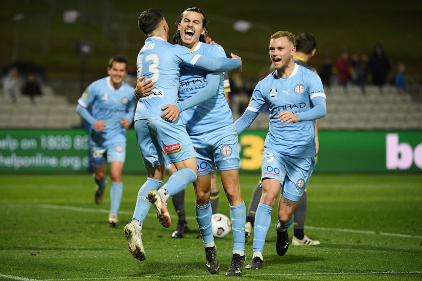 Two Melbourne City A-League players embrace as they celebrate a goal.