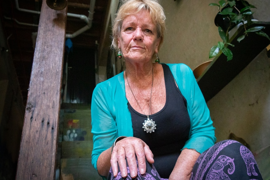 Portrait of an older woman sitting on wooden stairs with her hand on her knee