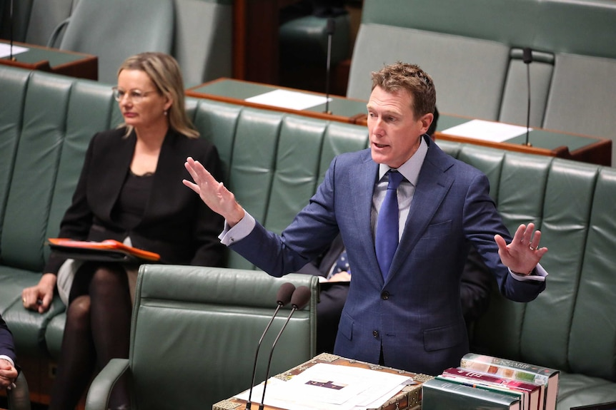 Christian Porter speaks at the despatch box with his arms outstretched. Sussan Ley is sitting behind him