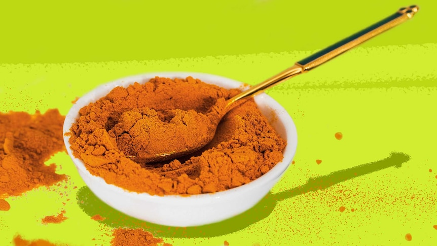 A small bowl of turmeric with a spoon in it