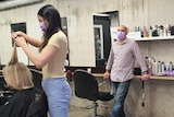 A female hairdresser wearing a face mask cuts a woman's hair, while a man wearing a face mask watches on.