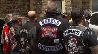 Bikies from various gangs show their colours with backs to the camera.