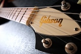 The Gibson guitar logo is shown up close on the guitar's head