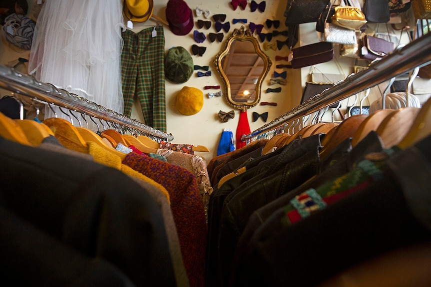 Vintage clothes, hats, bags and bow ties hang from the racks and walls.