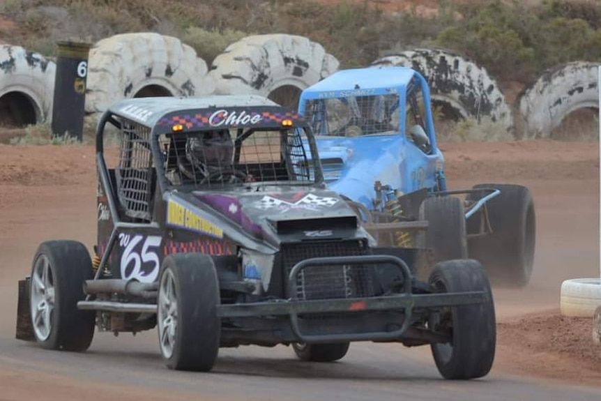 Black racing car in front of blue one on dirt track with big white tyres in background