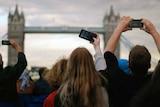 People crane to take photos of London Bridge.