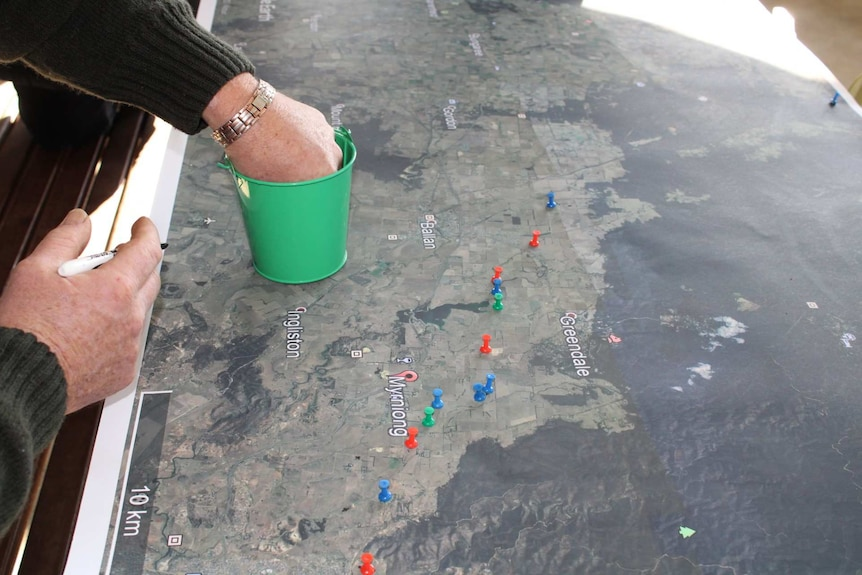A hand sticking coloured pins into a map