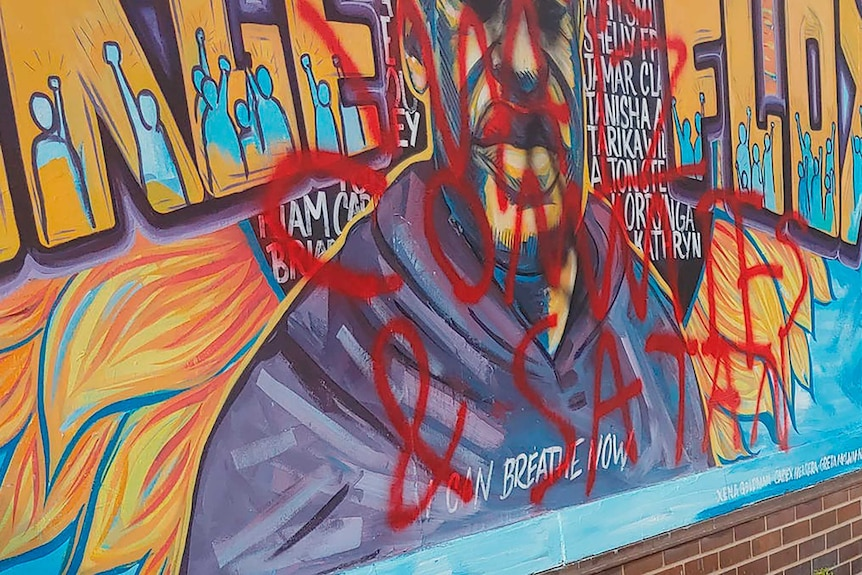 Mural dedicated to George Floyd has writing in spray painted in red over the picture.