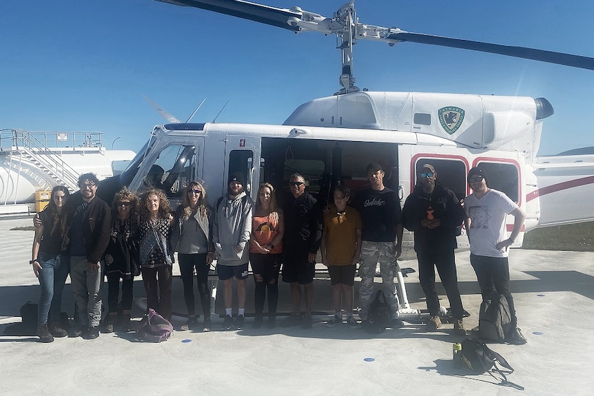 Members of Tasmania's Aboriginal community pose next to a helicopter.