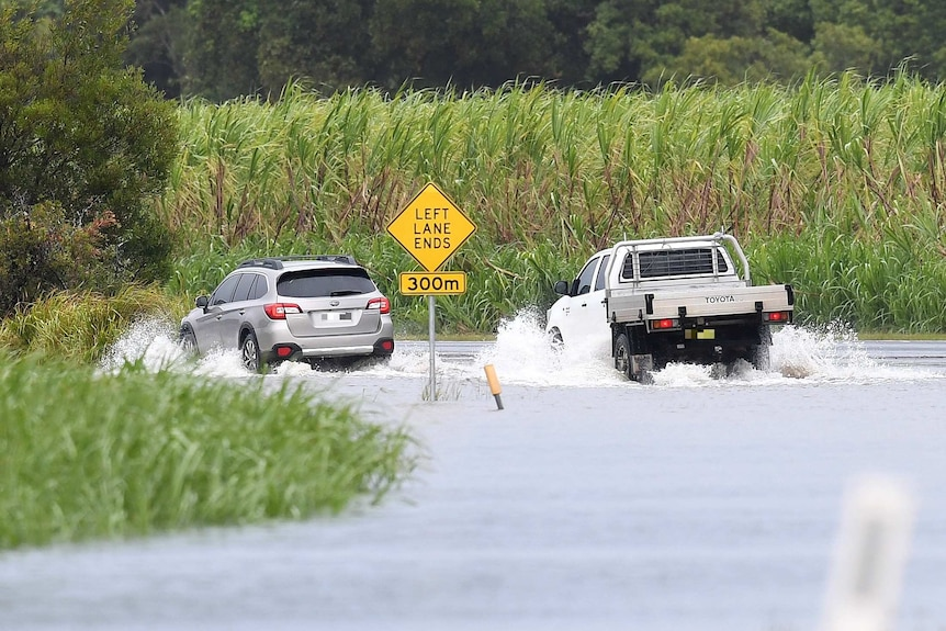 Cars drive through floodwaters at Tumbulgum.