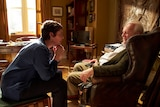 Olivia Colman and Anthony Hopkins talking in a lounge in The Father
