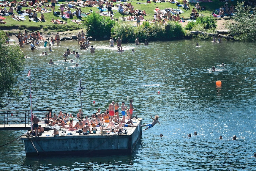 Crowds of people swim at a lake in Sweden.
