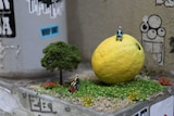 A miniature diorama consisting of a lemon and two elderly figurines