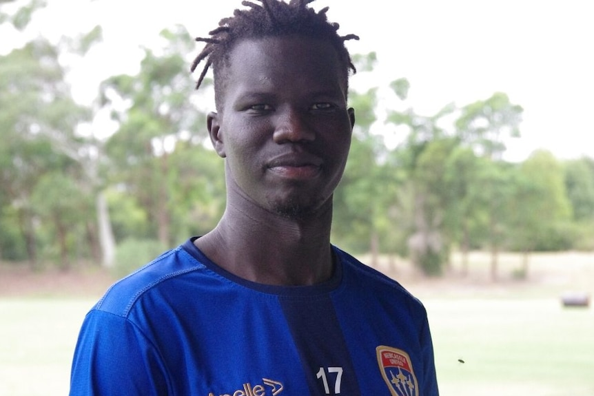 An African man in a sports top looks at the camera with trees in the background