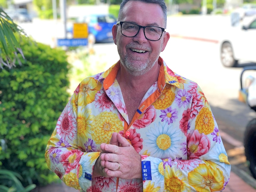 A man stands on a street smiling, wearing a bright floral shirt with parts of a blue ribbon placed discreetly on cuff and collar