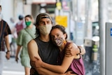 A man and woman, each wearing a mask, hold one another while walking in a city street.