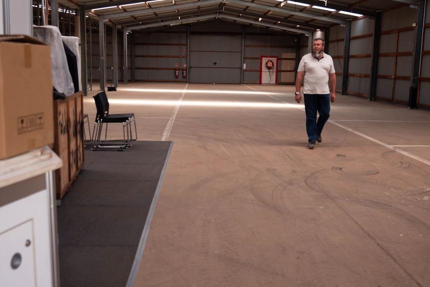 A man walks through an empty garage.