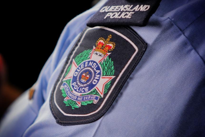 Queensland Police Service logo on shoulder sleeve of officer's shirt.