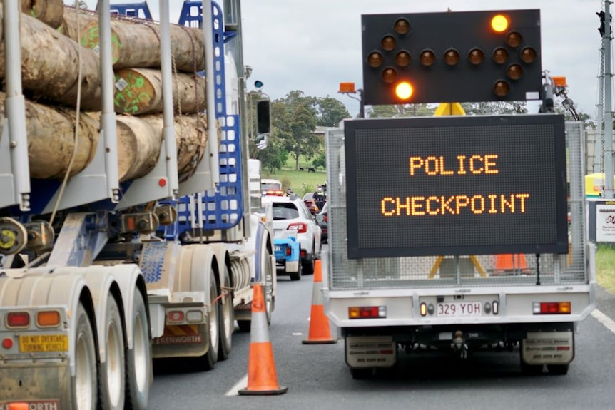 A logging truck waits behind a line of cars alongside a 'police checkpoint' sign.