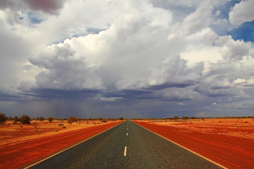 A stormy sky over a highway in the red dirt of central Australia.