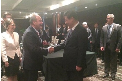 Two men shake hands surrounded by others in an official looking capacity.